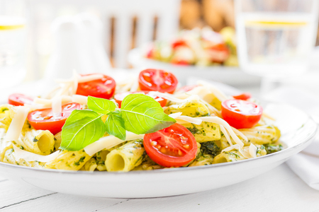 Pasta with basil pesto, tomato and cheese on plate Standard-Bild - 103953997