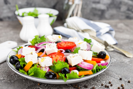 Greek salad. Fresh vegetable salad with tomato, onion, cucumbers, pepper, olives, lettuce and feta cheese. Greek salad on plate