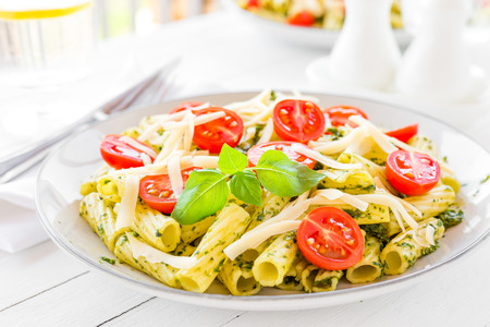 Pasta with basil pesto, tomato and cheese on plate Standard-Bild - 103953543