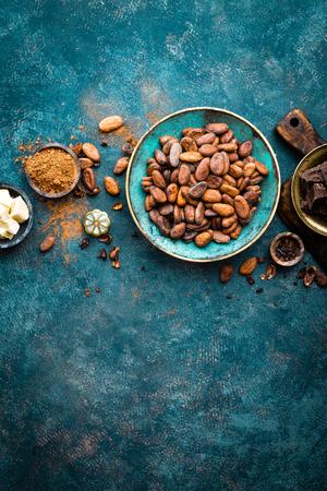 Cacao. Fèves de cacao, morceaux de chocolat noir amer, beurre de cacao et poudre de cacao. Fond de cacao