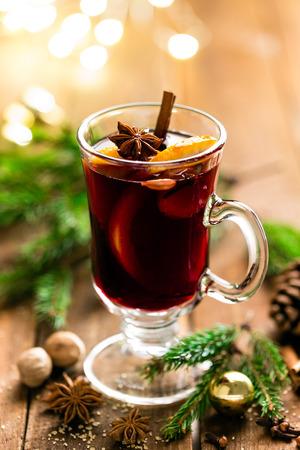 Kerst warme rode wijn met kruiden en sinaasappels op een rustieke houten tafel. Traditionele warme drank met Kerstmis Stockfoto