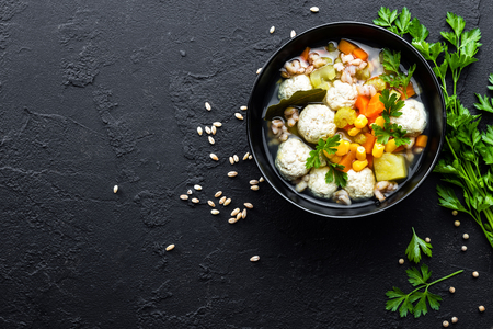 Delicious vegetable soup with chicken meatballs and pearl barley Фото со стока
