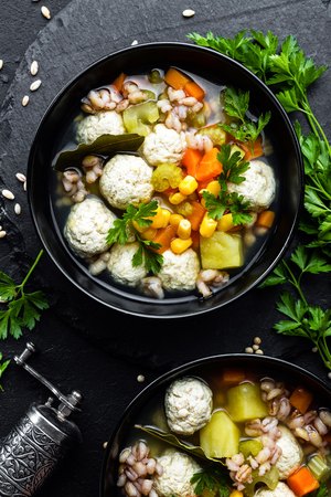 Delicious vegetable soup with chicken meatballs and pearl barley Фото со стока - 109105315