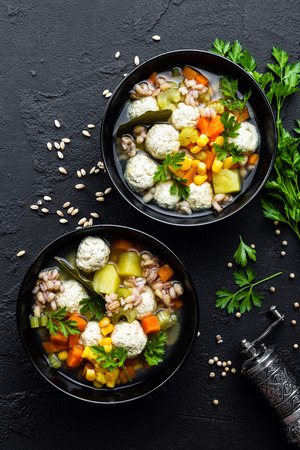 Delicious vegetable soup with chicken meatballs and pearl barley Фото со стока - 109105322