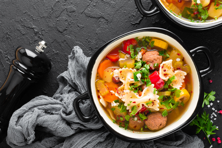 Italian minestrone soup with beef meatballs, vegetables and pasta in bowl
