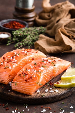 Fresh salmon fish fillet on wooden board Stock Photo - 112471571