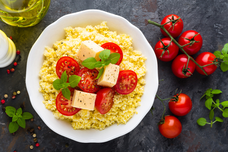 Millet porridge with tomatoes and cheese Standard-Bild