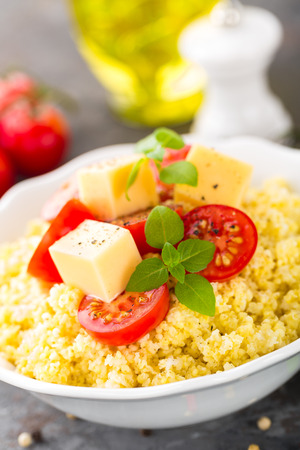Millet porridge with tomatoes and cheese Stock Photo