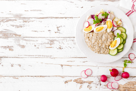 Oatmeal porridge with boiled egg and vegetable salad with fresh radish, cucumber and lettuce. Healthy dietary breakfast Reklamní fotografie