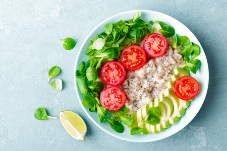 Oatmeal porridge with avocado and vegetable salad of fresh tomatoes and lettuce. Healthy dietary breakfast. Top view