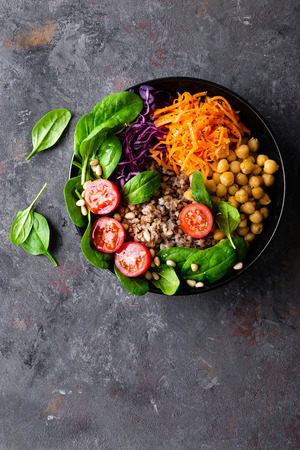 Healthy vegetarian dish with buckwheat and vegetable salad of chickpea, kale, carrot, fresh tomatoes, spinach leaves and pine nuts. Buddha bowl. Balanced food. Delicious detox diet.Top view Archivio Fotografico - 113255750