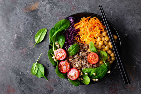 Healthy vegetarian dish with buckwheat and vegetable salad of chickpea, kale, carrot, fresh tomatoes, spinach leaves and pine nuts. Buddha bowl. Balanced food. Delicious detox diet.Top view Stock Photo - 113255814