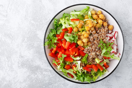 Healthy and delicious bowl with buckwheat and salad of chickpea, fresh pepper and lettuce leaves. Dietary balanced plant-based food. Vegan and vegetarian dish. Top view. Flat lay Stock Photo - 113647052