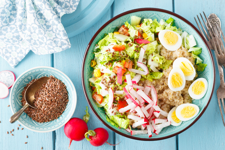 Bowl with wheat porridge, boiled quail eggs and fresh vegetable salad of radish, corn, sweet pepper and chinese cabbage. Healthy and delicious dietary lunch. Vegetarian, vegan food. Top view. Flat lay Stock Photo