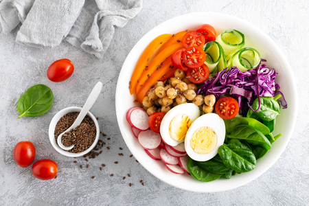 Buddha bowl salad with chickpeas, sweet pepper, tomato, cucumber, red cabbage kale, fresh radish, spinach leaves and boiled egg, healthy eating concept, top view, flat lay Stockfoto