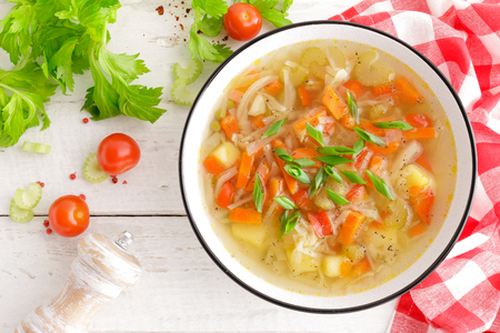 Vegetable soup. Healthy food, vegetarian dish. Vegetable soup with cabbage, potato, tomato, carrot, celery, pepper and green peas. Vegan diet menu. Top view Stock fotó