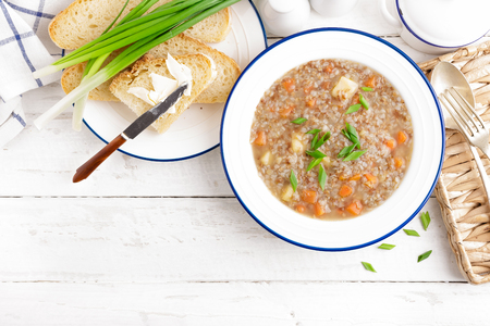 Buckwheat soup with carrot and potato on white wooden rustic table. Healthy vegetarian food, top view Zdjęcie Seryjne - 114360947