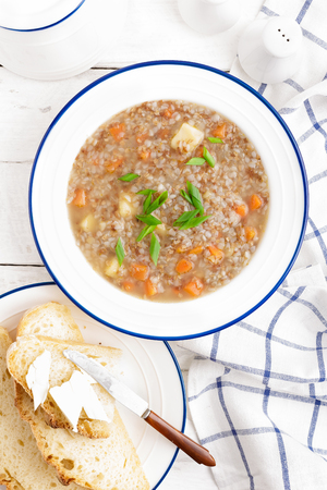 Buckwheat soup with carrot and potato on white wooden rustic table. Healthy vegetarian food, top view