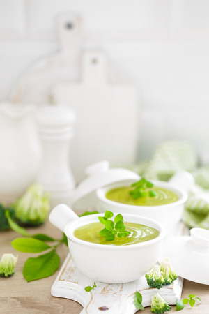 Broccoli soup in bowls on wooden kitchen table closeup. Healthy vegetarian dish. Diet food