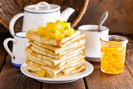 Homemade thin crepes with orange jam, stack of pancakes on wooden rustic background Imagens
