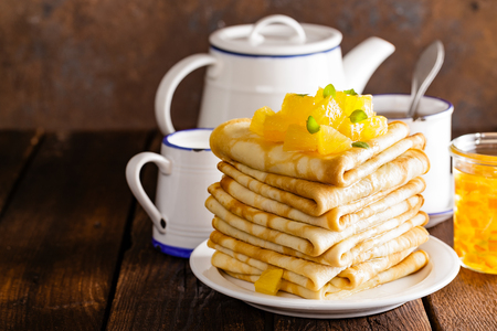 Homemade thin crepes with orange jam, stack of pancakes on wooden rustic background Stock Photo