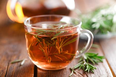 Rosemary tea in glass tea cup on rustic wooden table closeup. Herbal vitamin tea. 免版税图像
