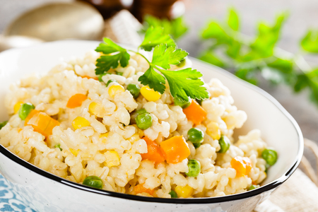 Bulgur wheat boiled with carrot, green peas and corn, healthy vegan diet