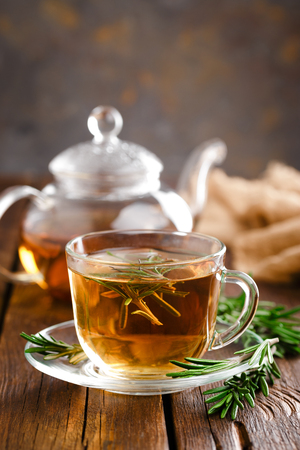 Rosemary tea in glass tea cup on rustic wooden table closeup. Herbal vitamin tea. Banque d'images