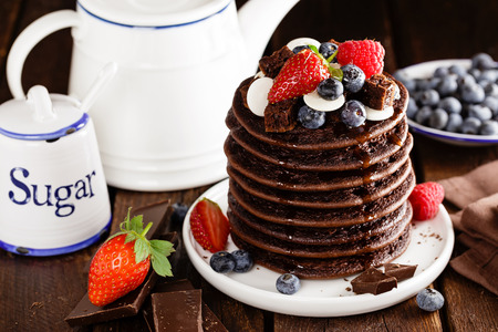 Stack of chocolate pancakes with berries, strawberry, raspberry and blueberry 免版税图像