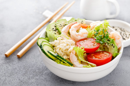 Hawaiian poke bowl with shrimps, rice and vegetables, healthy Buddha bowl with prawns, rice, avocado, cucumber, tomato and lettuce Foto de archivo