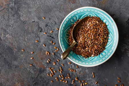 Flax seeds in bowl on dark background closeup top view Stockfoto