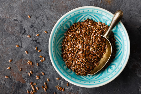 Flax seeds in bowl on dark background closeup top view Zdjęcie Seryjne