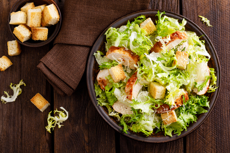 Caesar salad with grilled chicken meat, fresh lettuce, parmesan cheese and fried croutons. Classic North American cuisine. Top view Stock Photo