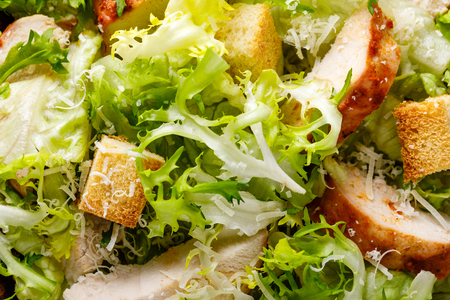 Caesar salad with grilled chicken meat, fresh lettuce, parmesan cheese and fried croutons. Classic North American cuisine.
