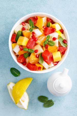 Gezonde vegetarische verse fruitsalade met appel, peer, mandarijn, grapefruit, mango, granaatappel en citroensap