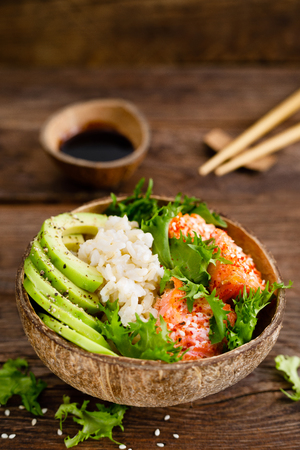 Hawaiian poke coconut bowl with grilled salmon fish, rice and avocado. Healthy food Stock Photo