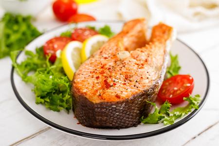 Filete de salmón a la plancha y ensalada de verduras frescas con tomate y lechuga. Comida sana. Vista superior
