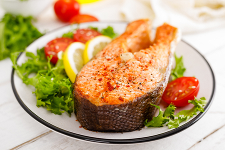 Salmon fish steak grilled and fresh vegetable salad with tomato and lettuce. Healthy food. Top view 免版税图像