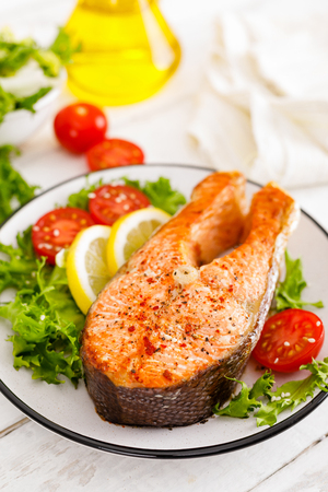 Salmon fish steak grilled and fresh vegetable salad with tomato and lettuce. Healthy food. Top view Stock Photo