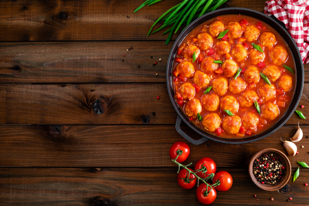 Chicken meatballs in spicy tomato sauce with vegetables in pan. Mexican cuisine Stock Photo