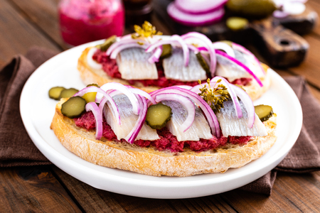 Delicious grilled sandwiches with herring, onion and beetroot sauce with horseradish on dark wooden rustic background. Danish cuisine Banco de Imagens