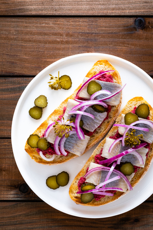Delicious grilled sandwiches with herring, onion and beetroot sauce with horseradish on dark wooden rustic background. Danish cuisine. Top view