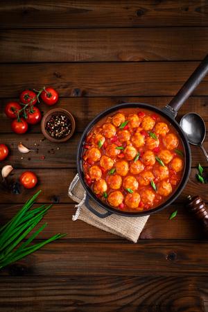Chicken meatballs in spicy tomato sauce with vegetables in pan. Mexican cuisine Foto de archivo - 116635122
