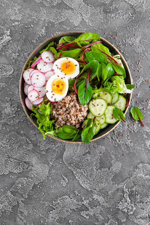 Buddha bowl dish with buckwheat porridge, boiled egg, fresh vegetable salad of radish, cucumber, lettuce and chard leaves. Healthy lunch menu. Top view
