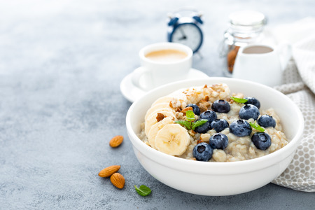 Oatmeal with fresh blueberry, banana, almond nuts and honey for breakfast Foto de archivo - 118170163