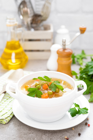 Summer light vegetarian vegetable soup with carrot, potato, cabbage and grean peas on white background. Diet healthy and tasty lunch. Baby food Archivio Fotografico