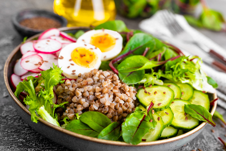 Buddha bowl dish with buckwheat porridge, boiled egg, fresh vegetable salad of radish, cucumber, lettuce and chard leaves. Healthy lunch menu