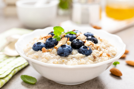 Oatmeal with fresh blueberry, almond nuts and honey for breakfast