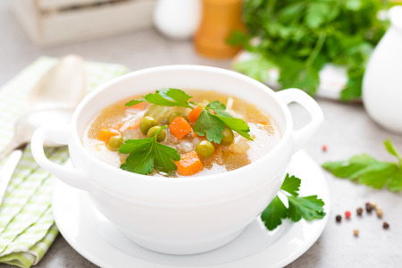 Summer light vegetarian vegetable soup with carrot, potato, cabbage and grean peas on white background. Diet healthy and tasty lunch. Baby food