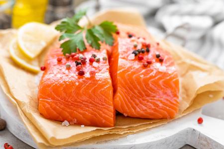 Fresh raw salmon fish fillet on white kitchen background